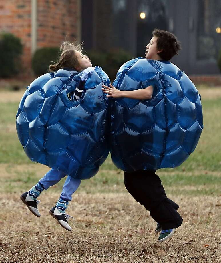 Follow the bouncing children: Grace, 9, and Jack Brennon, 12, wearing their Buddy Bumper Balls Christmas presents, collide in Richmond, Va. Photo: Bob Brown, Associated Press