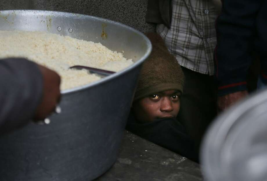 Hungry eyes:In New Delhi, a homeless boy waits below a table at a free-food distribution. Photo: Manish Swarup, Associated Press