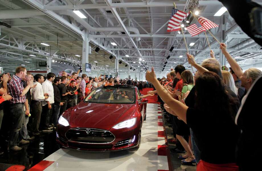 FILE - In this June 22, 2012 file photo, Tesla workers cheer on one the first Tesla Model S cars sold during a rally at the Tesla factory in Fremont, Calif. A healthier economy and more new model introductions should push U.S. auto sales above the 15 million mark in 2013, predicts an auto industry research firm. The Polk research firm says auto sales should continue to lead the country's economic recovery, rising nearly 7 percent over 2012 to 15.3 million new vehicle registrations. (AP Photo/Paul Sakuma, File) Photo: Paul Sakuma