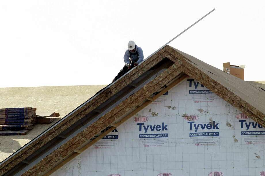 In this Nov. 28, 2012 photo, a worker constructs a home in Chicago. U.S. builders spent less on construction projects in November, the first decline in eight months, as activity was held back by a big drop in spending on federal projects. (AP Photo/Nam Y. Huh) Photo: Nam Y. Huh