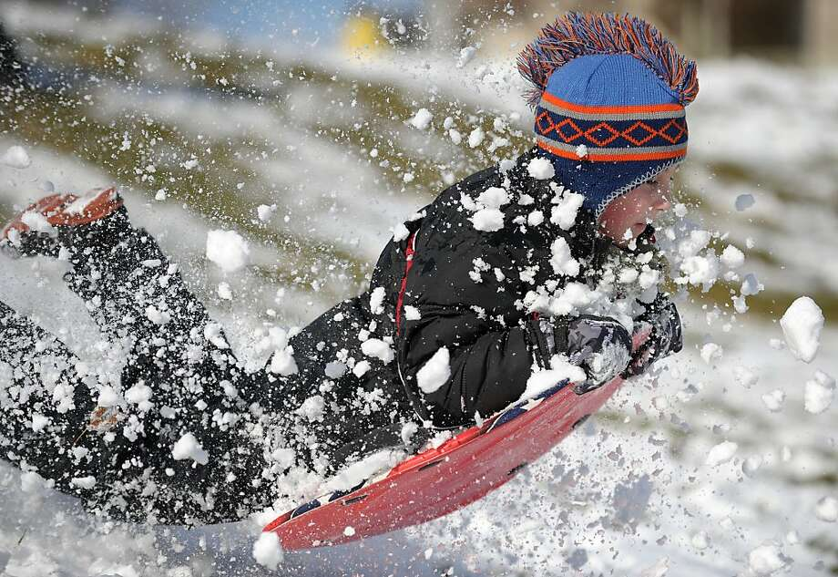 Identified flying object: A flying saucer makes a bumpy landing in the snow in Lopatcong Township, Pa. Piloting it is 9-year-old Adam Hlinka. Photo: Matt Smith, Associated Press