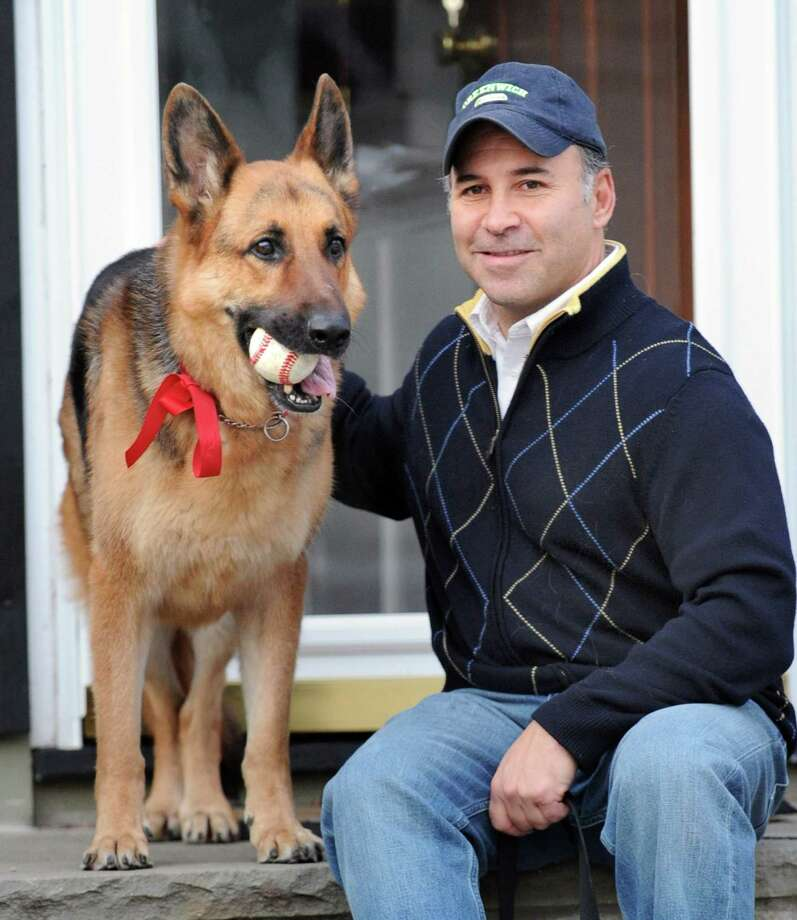 State Rep. Alfred Camillo, R-151st District, with his German shepherd, Rudy, on the front steps of his Old Greenwich home, Wednesday afternoon, Jan. 2, 2013. Greenwich town policy does not allow evacuees to bring their pets, other than service dogs, to local shelters during emergencies. Camillo along with other elected officials are trying to change that. Photo: Bob Luckey / Greenwich Time