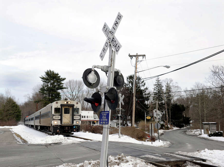 A Metro North train heading south approaches the Long Ridge Road crossing in West Redding where another train struck a car on Sunday, killing one person and injuring three others. Photo: Carol Kaliff / The News-Times