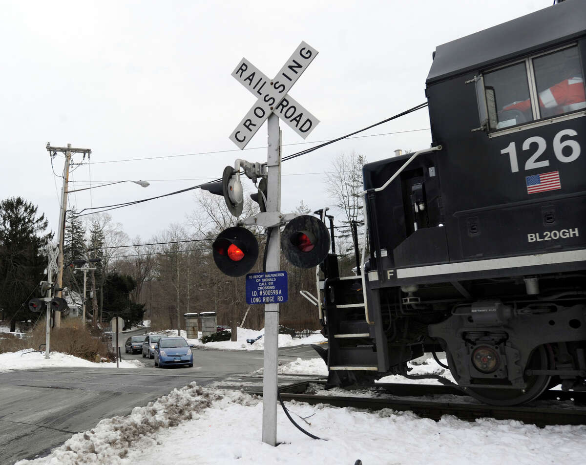 Cars coming from Long Ridge Road stop at a railroad crossing for a Metro-North train heading north, Wednesday, January 2, 2013.