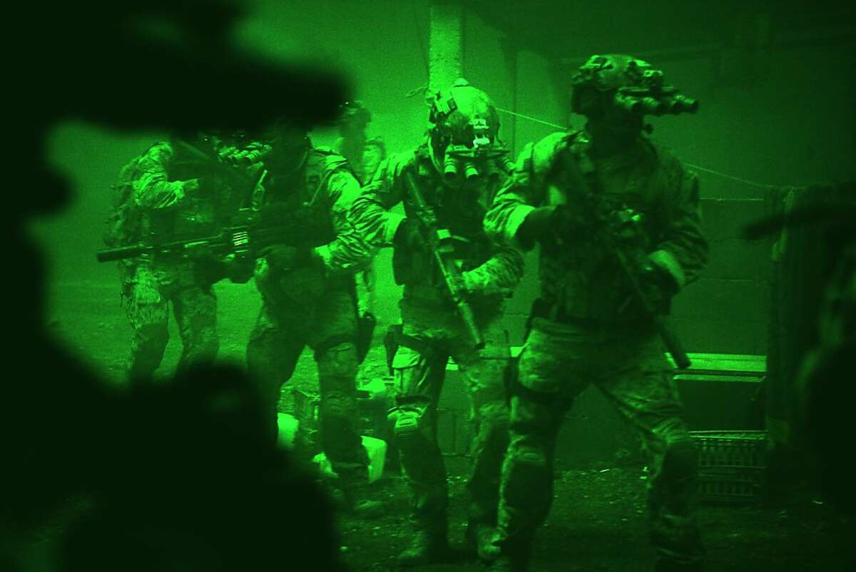 Seen through the greenish glow of night vision goggles, Navy SEALs prepare to breach a locked door in Osama Bin Laden's compound in Columbia Pictures' hyper-realistic new action thriller from director Kathryn Bigelow, ZERO DARK THIRTY.