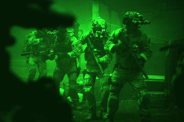 Seen through the greenish glow of night vision goggles, Navy SEALs prepare to breach a locked door in Osama Bin Laden's compound in Columbia Pictures' hyper-realistic new action thriller from director Kathryn Bigelow, ZERO DARK THIRTY. Photo: Jonathan Olley, Columbia Pictures