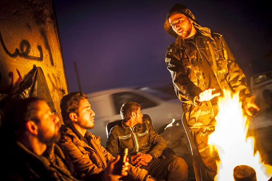 Syrian rebels gather around a fire as they plan patrols in Aleppo, Syria. The U.N. says the sectarian nature of the war makes it all the harder to stop. Photo: Andoni Lubaki, Associated Press