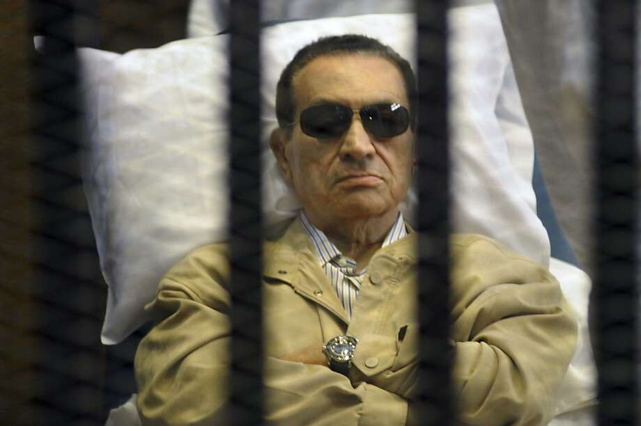Ex-President Hosni Mubarak lay on a gurney inside a barred cage during his trial. Photo: Anonymous, Associated Press