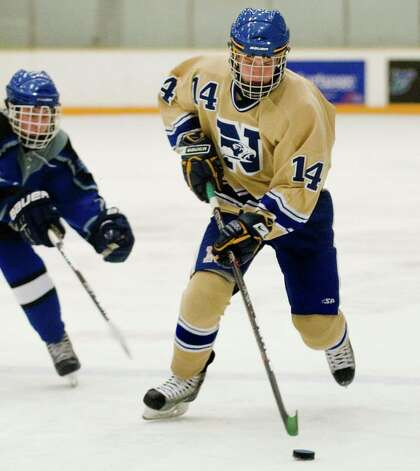 Newtown High School's Chris Erikson carries the puck in a game against East Catholic High School, played at the Danbury Arena. Wednesday, Jan. 2, 2013 Photo: Scott Mullin