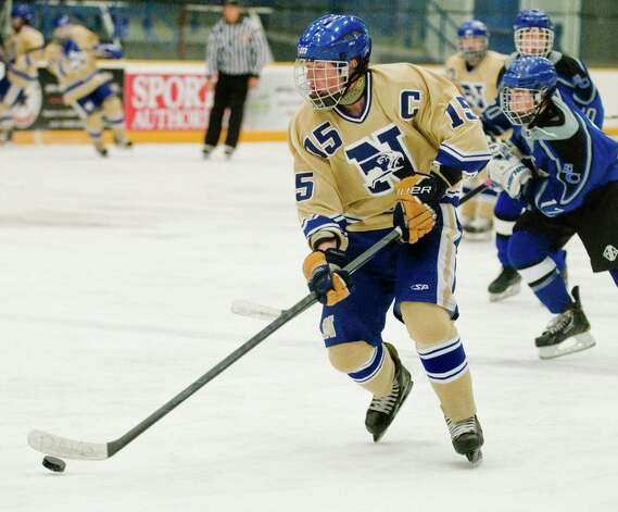 Newtown High School's Evan Isaacs carries the puck into the East Catholic High School offensive zone in a game at the Danbury Arena. Wednesday, Jan. 2, 2013 Photo: Scott Mullin