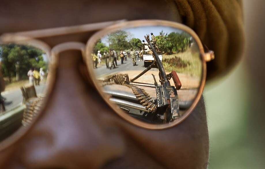 "A Chadian soldier wearing reflective sunglasses observes the convoy ahead of him, as Chadian soldiers who are fighting in support of Central African Republic president Francois Bozize, ride on the road leading to Damara, about 70km (44 miles) north of the capital Bangui, Central African Republic Wednesday, Jan. 2, 2013. More than 30 truckloads of troops from Chad line the two-lane highway just outside of Damara, supporting government forces who want to block a new rebel coalition from reaching the capital, and Gen. Jean Felix Akaga, who heads a 10-nation regional force, says the town is a ""red line that the rebels cannot cross"" or his forces will attack. Photo: Ben Curtis, Associated Press"