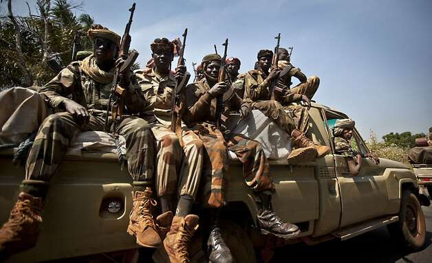 "Chadian soldiers who are fighting in support of Central African Republic president Francois Bozize, ride on a truck full of weapons in a convoy on the road leading to Damara, about 70km (44 miles) north of the capital Bangui, Central African Republic Wednesday, Jan. 2, 2013. More than 30 truckloads of troops from Chad line the two-lane highway just outside of Damara, supporting government forces who want to block a new rebel coalition from reaching the capital, and Gen. Jean Felix Akaga, who heads a 10-nation regional force, says the town is a ""red line that the rebels cannot cross"" or his forces will attack. (AP Photo/Ben Curtis) Photo: Ben Curtis, Associated Press"