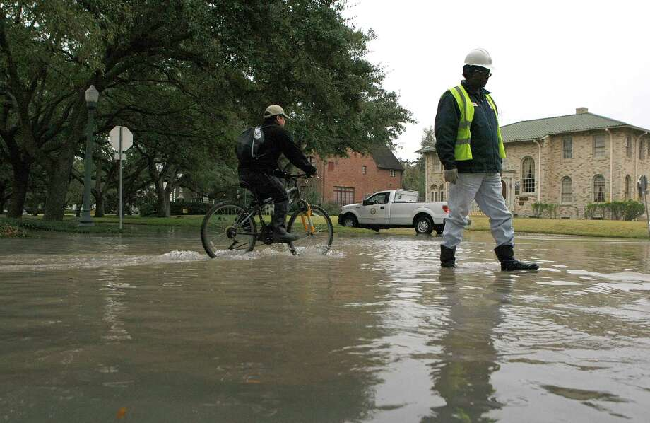 A utility worker walks through flood waters on the corner of North Blvd. at Woodhead Street as a water main break caused flooding along the block on North Blvd. between Woodhead and Hazard Streets Wednesday, Jan. 2, 2013, in Houston. Photo: Johnny Hanson, Houston Chronicle / © 2012  Houston Chronicle