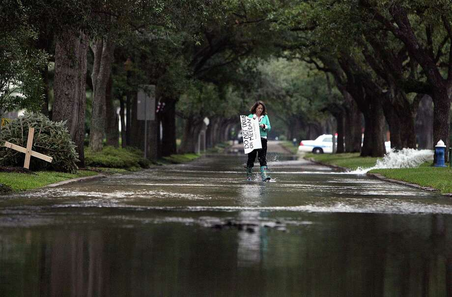 Resident Mary Flood Nugent walks across a flooded North Blvd. holding a sign to warn people not to drive over the median if fear that it may harm the live oak trees that line the flooded road between Woodhead and Hazard Streets Wednesday, Jan. 2, 2013, in Houston. Photo: Johnny Hanson, Houston Chronicle / © 2012  Houston Chronicle