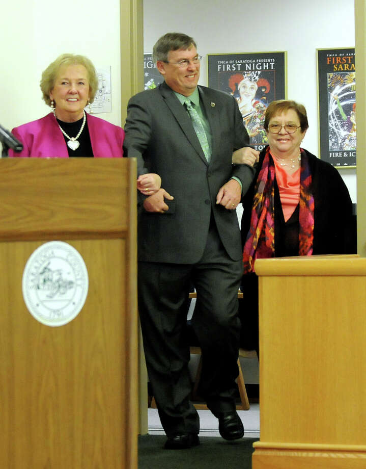 Supervisors Mary Ann Johnson, left, and Jean Raymond, right, escort Alan Grattidge, center, for his swearing-in ceremony to become chairman of the Saratoga County Board of Supervisors on Wednesday, Jan. 2, 2013, at the Saratoga County Building in Ballston Spa, N.Y. (Cindy Schultz / Times Union) Photo: Cindy Schultz / 00020621A