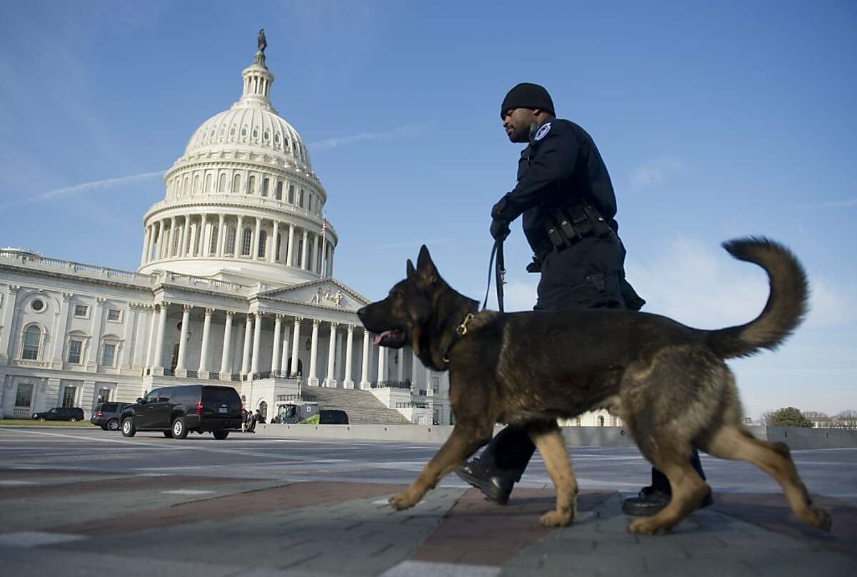 A US Capitol Police Officer and a police dog patrol in front of the US Capitol in Washington, DC, on January 2, 2013, on the day after a compromise bill passed the US Congress, avoiding the