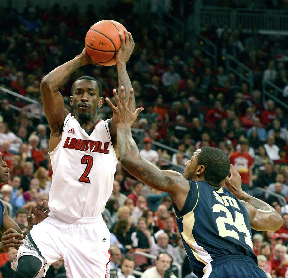Louisville's Russ Smith, left, looks to pass over the defense of Florida International's Malik Smith during the second half of an NCAA college basketball game on Wednesday, Dec. 19, 2012, in Louisville, Ky. Louisville defeated FIU 79-55. (AP Photo/Timothy D. Easley) Photo: Timothy D. Easley, Associated Press / FR43398 AP