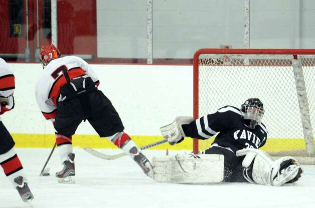 At left, Brian Silard, # 7 of Greenwich, dekes Xavier goalie Shane Baldwin, who falls to the ice, before Silard scored the first goal of the game in the boys high school hockey game between Greenwich and Xavier of Middletown, Conn., at Dorothy Hamill Rink, Wednesday night, Jan. 2, 2013. Photo: Bob Luckey / Greenwich Time