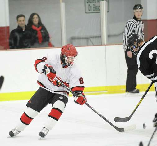 At left, Mark Schmeiler # 8 of Greenwich goes for the puck during the boys high school hockey game between Greenwich and Xavier of Middletown, Conn., at Dorothy Hamill Rink, Wednesday night, Jan. 2, 2013. Photo: Bob Luckey / Greenwich Time