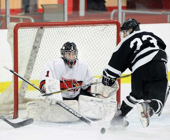 At left, Greenwich goalie Bryan Archino blocks the point-blank shot of Ryan McLellan, # 23 of Xavier, during the boys high school hockey game between Greenwich and Xavier of Middletown, Conn., at Dorothy Hamill Rink, Wednesday night, Jan. 2, 2013. Photo: Bob Luckey / Greenwich Time