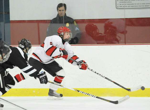At right, Kevin Piotrzkowski, # 2 of Greenwich, advances the puck during the boys high school hockey game between Greenwich and Xavier of Middletown, Conn., at Dorothy Hamill Rink, Wednesday night, Jan. 2, 2013.  Attempting the stick-check for Xavier is Ryan McLellan # 23. Photo: Bob Luckey / Greenwich Time