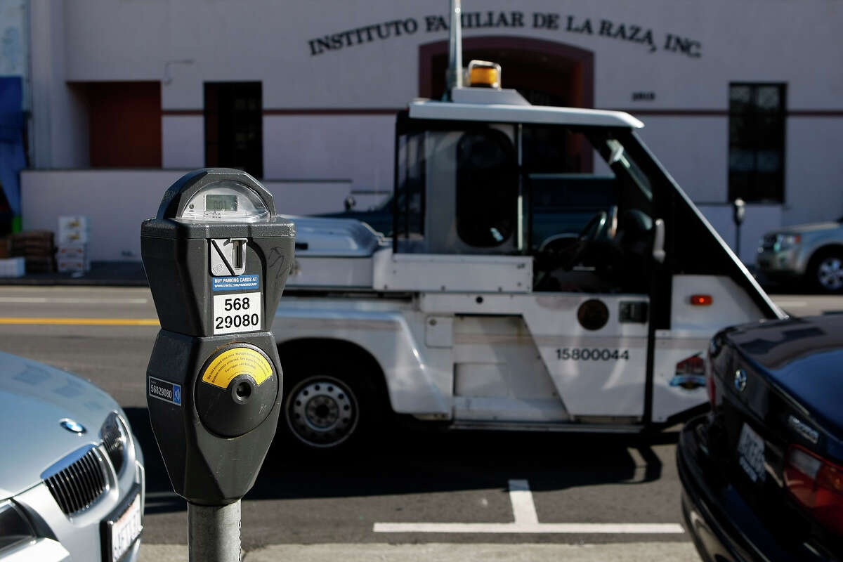 Parking control officer Eric Viana checks meters along Mission Street. San Francisco street parking no longer costs on Sundays.