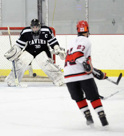 At left, Xavier goalie Shane Baldwin blocks a shot by Matt Lodato, right, # 23 of Greenwich, during the first period of the boys high school hockey game between Greenwich and Xavier of Middletown, Conn., at Dorothy Hamill Rink, Wednesday night, Jan. 2, 2013. Photo: Bob Luckey / Greenwich Time