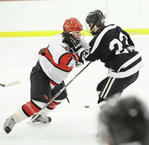 At left, Alex Bastone of Greenwich checks Ryan McLellan # 23 of Xavier during the boys high school hockey game between Greenwich and Xavier of Middletown, Conn., at Dorothy Hamill Rink, Wednesday night, Jan. 2, 2013. Photo: Bob Luckey / Greenwich Time