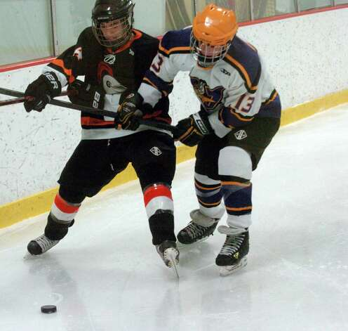 Stamford's Michael Zarrilli, left, and Westhill's Scott Reville in action as Stamford and Westhill HIgh Schools face off in a boys hockey game at Terry Conners Ice Rink in Stamford, Conn., Jan. 2, 2012. Photo: Keelin Daly / Stamford Advocate Riverbend Stamford, CT