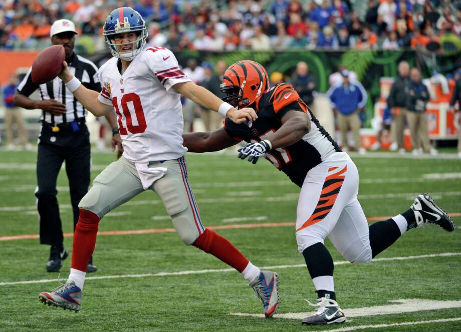 FILE - In this Nov. 11, 2012, file photo, New York Giants quarterback Eli Manning (10) is pursued by Cincinnati Bengals defensive tackle Geno Atkins during the second half of an NFL football game in Cincinnati. Atkins gets a lot of attention every time an opponent watches film trying to figure out how to contain the Bengals defensive tackle. His first selection as a Pro Bowl starter shows what they think of him. (AP Photo/Michael Keating, File) Photo: Michael Keating