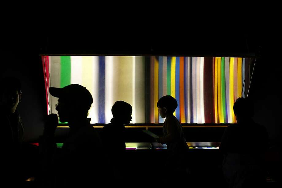 Visitors check out the Aurora exhibit of changing colors on a screen during the old Exploratorium's last day. Photo: Sarah Rice, Special To The Chronicle