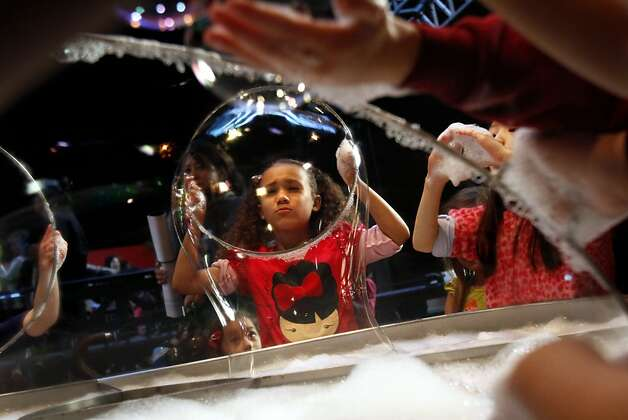 Raven Placido, 7, of Castro Valley, makes giant bubbles on the last day the Exploratorium is open at the Palace of Fine Arts. Photo: Sarah Rice, Special To The Chronicle
