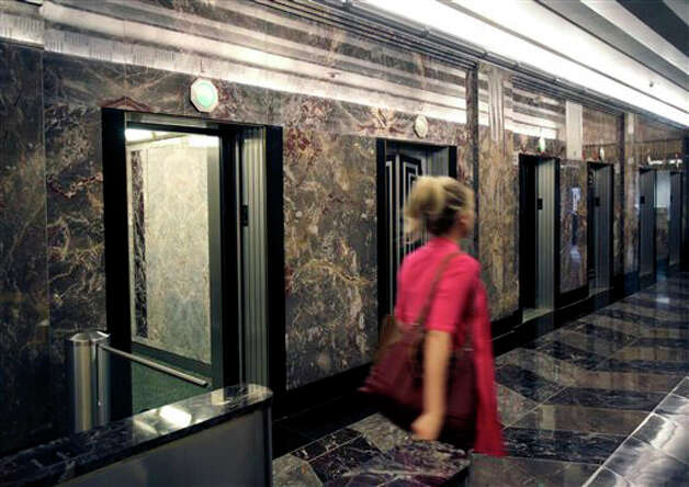 A woman walks past a bank of elevators in the Empire State Building in New York in this file photo. Photo: Seth Wenig, ST / AP2011