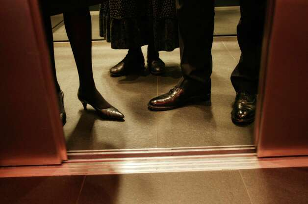 Employees ride the elevator in an office in this file photo. Photo: SUZANNE PLUNKETT, Bloomberg / Bloomberg
