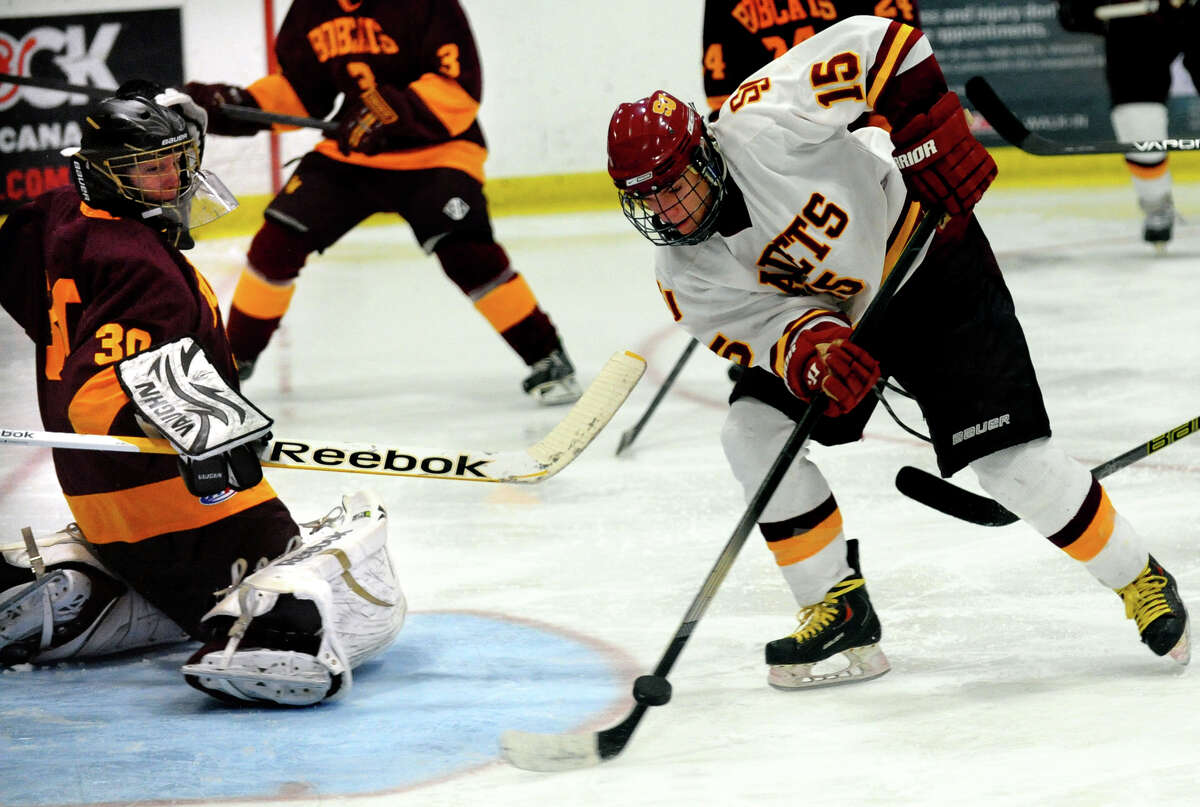 The puck is deflected by South Windsor goalie Aidan Cain as St. Joseph's #15 Ryan Corcoran attempts to score, during boys hockey action at The Rinks in Shelton, Conn. on Wednesday January 2, 2012.