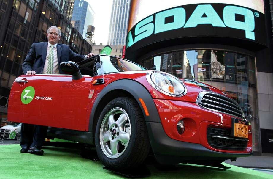 FILE - In this April 14, 2011 file photo provided by Zipcar.com, Zipcar Chairman and CEO Scott Griffith stands with a Zipcar Mini-Cooper before the opening bell at the NASDAQ Market Site in New York. Avis is buying Zipcar for $491.2 million, expanding its offerings from traditional car rentals to car sharing services. The boards of both companies unanimously approved the buyout. (AP Photo/Zipcar.com, Craig Ruttle, File) Photo: Craig Ruttle