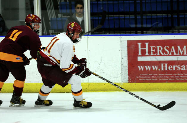 St. Joseph's #11 Sean Hurley corrals the puck with South Windsor's #11 Rick Landino at his back, during boys hockey action at The Rinks in Shelton, Conn. on Wednesday January 2, 2012. Photo: Christian Abraham / Connecticut Post