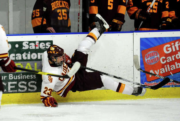 St. Joseph's #23 Sean Smith takes a spill along the rails, during boys hockey action against South Windsor at The Rinks in Shelton, Conn. on Wednesday January 2, 2012. Photo: Christian Abraham / Connecticut Post