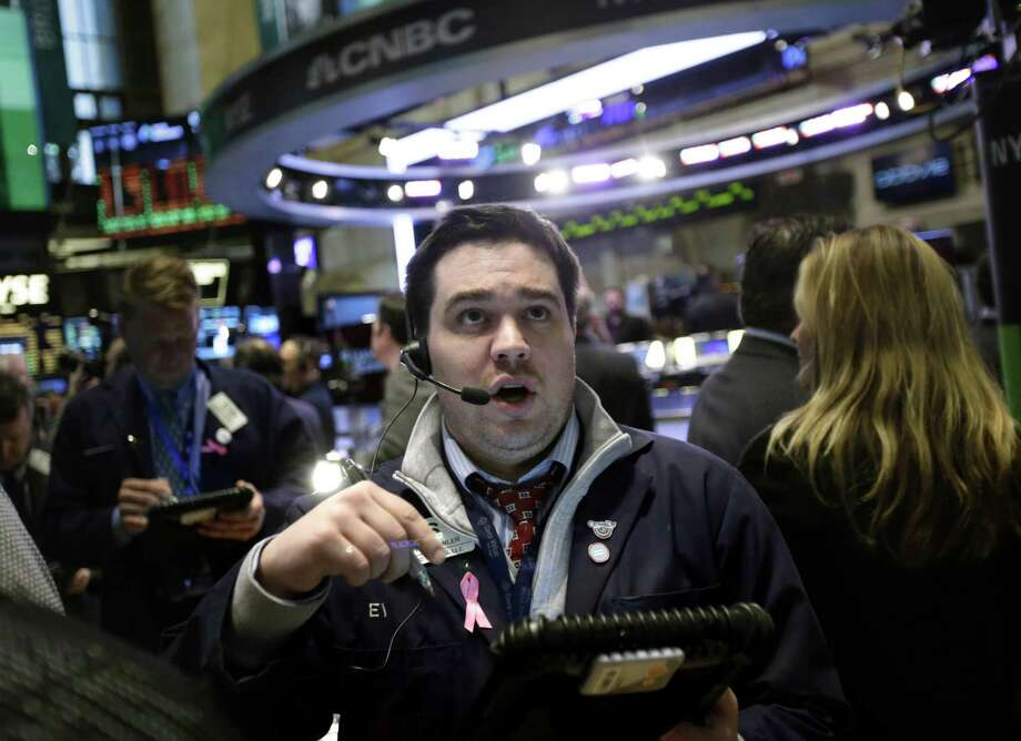 "A trader works on the floor at the New York Stock Exchange in New York, Wednesday, Jan. 2, 2013. The ""fiscal cliff"" compromise, for all its chaos and controversy, was enough to send the stock market shooting higher Wednesday, the first trading day of the new year. (AP Photo/Seth Wenig) Photo: Seth Wenig"