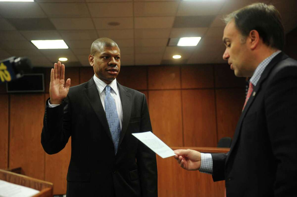 New police officer Alberto E. Escoffery, is sworn by First Selectman Peter Tesei at Greenwich Town Hall in Greenwich, Conn., Wednesday, Jan. 2, 2013.