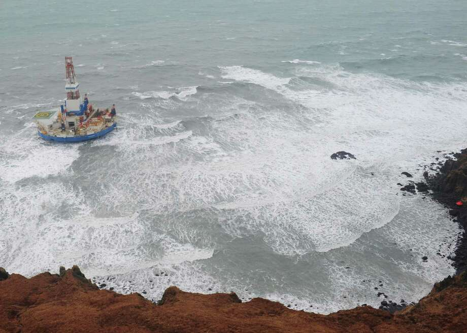 This aerial image provided by the U.S. Coast Guard shows the Royal Dutch Shell drilling rig Kulluk aground off a small island near Kodiak Island Tuesday Jan. 1, 2013. No leak has been seen from the drilling ship that grounded off the island during a storm, officials said Wednesday, as opponents criticized the growing race to explore the Arctic for energy resources. (AP Photo/U.S. Coast Guard) Photo: Sara Francis, HOPD / US Coast Guard
