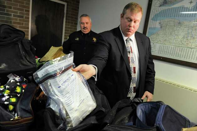 Detective Scott Gillis, center, and Undersheriff John Winchell, left, show bags of evidence on Wednesday, Jan. 2, 2013, at Hudson Falls Village Hall in Hudson Falls, N.Y. Thousands of pieces of stolen property have been found. (Cindy Schultz / Times Union) Photo: Cindy Schultz / 00020629A