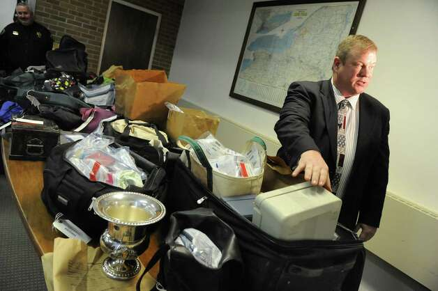 Detective Scott Gillis, right, shows bags of evidence on Wednesday, Jan. 2, 2013, at Hudson Falls Village Hall in Hudson Falls, N.Y. Gillis estimates that $100,000 worth of stolen property are on the table. (Cindy Schultz / Times Union) Photo: Cindy Schultz / 00020629A