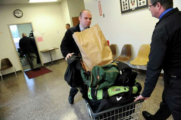 Glens Falls detective sergeants Seth French, center, and  Peter Casertino help wheel out bags of stolen property following a news conference on Wednesday, Jan. 2, 2013, at Hudson Falls Village Hall in Hudson Falls, N.Y. (Cindy Schultz / Times Union) Photo: Cindy Schultz / 00020629A