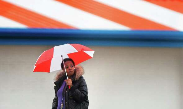 Tiffany Cobbin shields herself from the rain as she waits for the bus on N Main Street, Wednesday, Jan. 2, 2013, in Houston. The forecast calls to be in the 40s throughout the day, have few showers on Friday and will stay in the 50s until Sunday. Photo: Cody Duty, Houston Chronicle / © 2012 Houston Chronicle