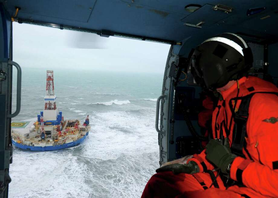 This aerial image provided by the U.S. Coast Guard shows Rear Adm. Thomas Ostebo, Incident Management Team commander, observing the Royal Dutch Shell drilling rig Kulluk aground during an overflight off a small island near Kodiak Island Tuesday Jan. 1, 2013. No leak has been seen from the drilling ship that grounded off the island during a storm, officials said Wednesday, as opponents criticized the growing race to explore the Arctic for energy resources. (AP Photo/U.S. Coast Guard, Sara Francis) Photo: Sara Francis