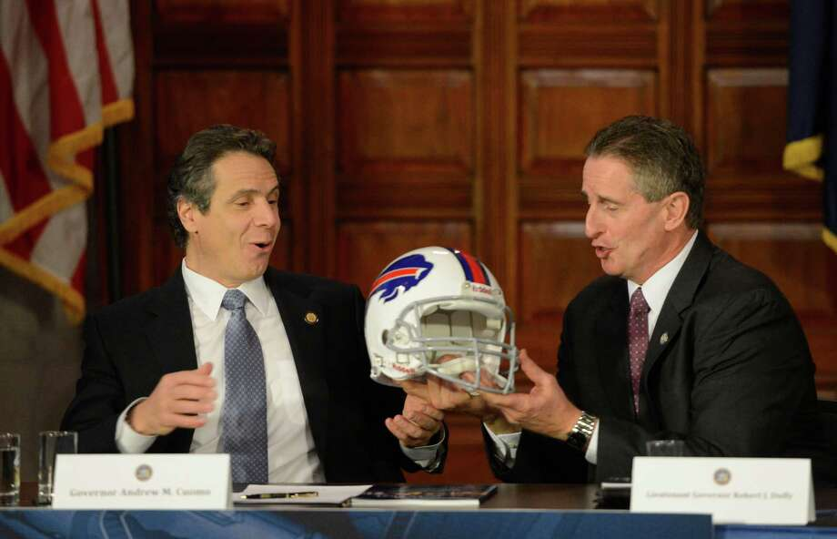 Governor Andrew Cuomo, left receives a Buffalo Bill helmet from Lt. Governor Robert Duffy during a cabinet meeting in the State Capitol in Albany, N.Y. Jan 2, 2013 after work was done to make sure that the pro football team remained in Buffalo for at least another 7 years.(Skip Dickstein/Times Union) Photo: SKIP DICKSTEIN / 00020630A