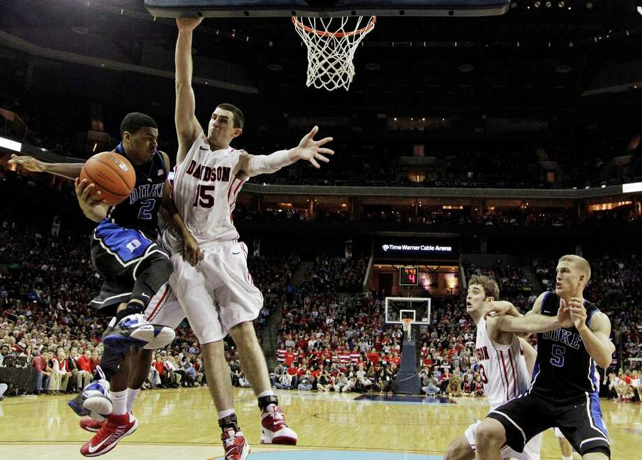 Duke's Quinn Cook (2) looks to pass to Mason Plumlee (5) as Davidson's Jake Cohen (15) and Tom Droney (23) defend during the second half of an NCAA college basketball game in Charlotte, N.C., Wednesday, Jan. 2, 2013. Duke won 67-50. (AP Photo/Chuck Burton) Photo: Chuck Burton