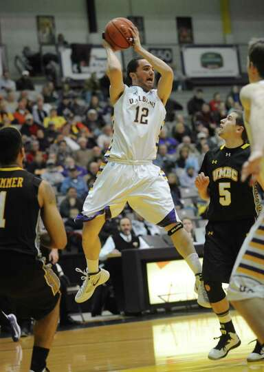 UAlbany's Peter Hooley passes the ball  during their men's college basketball game against UMBC at t