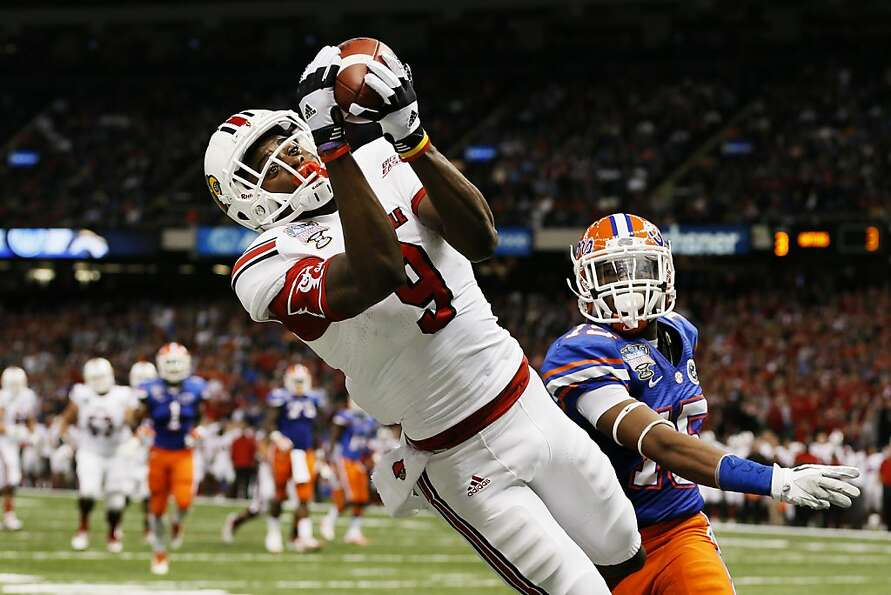 Louisville's DeVante Parker catches a touchdown pass over Florida's Loucheiz Purifoy in the second q